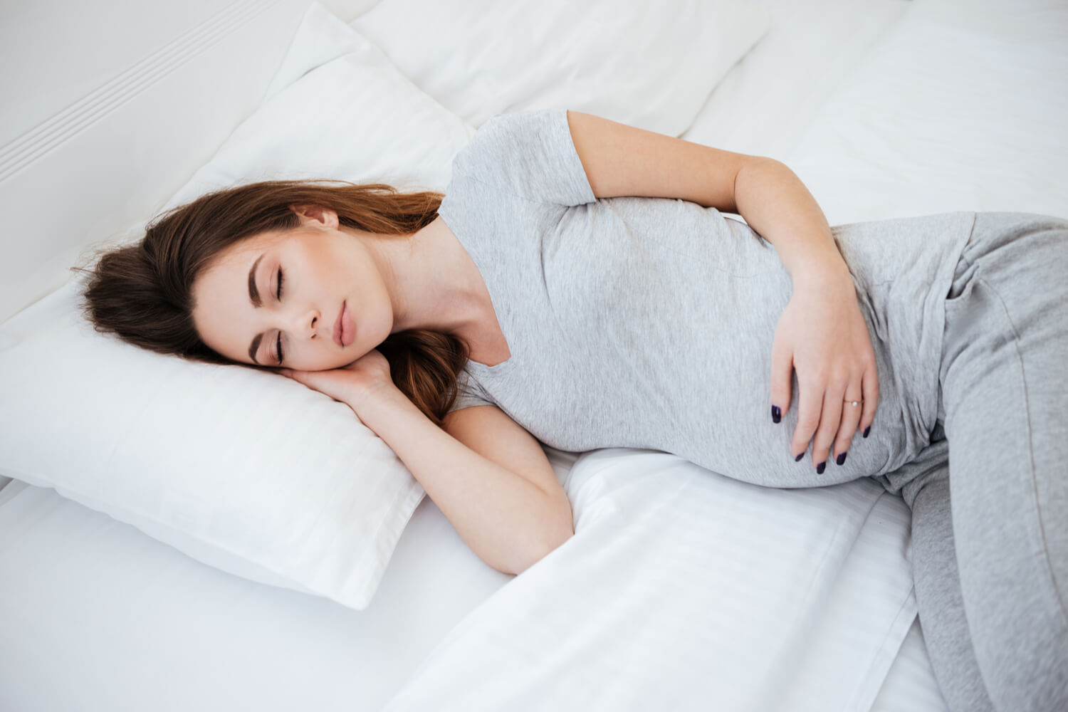 pregnant women sleeping on bed