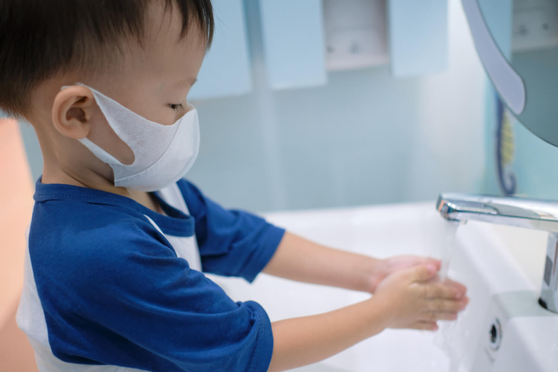 toddler in mask washing hands