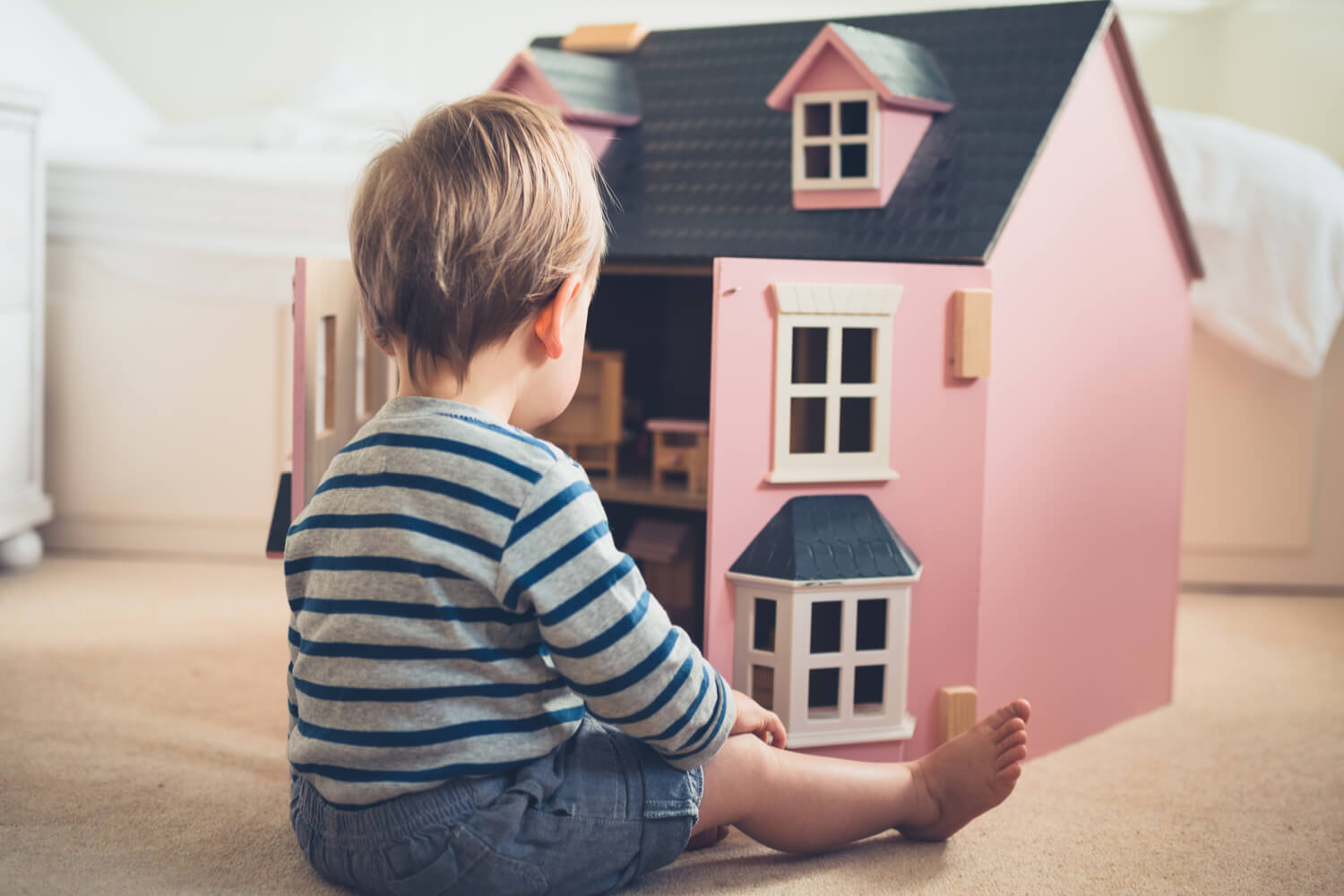 boy playing with a pink doll house