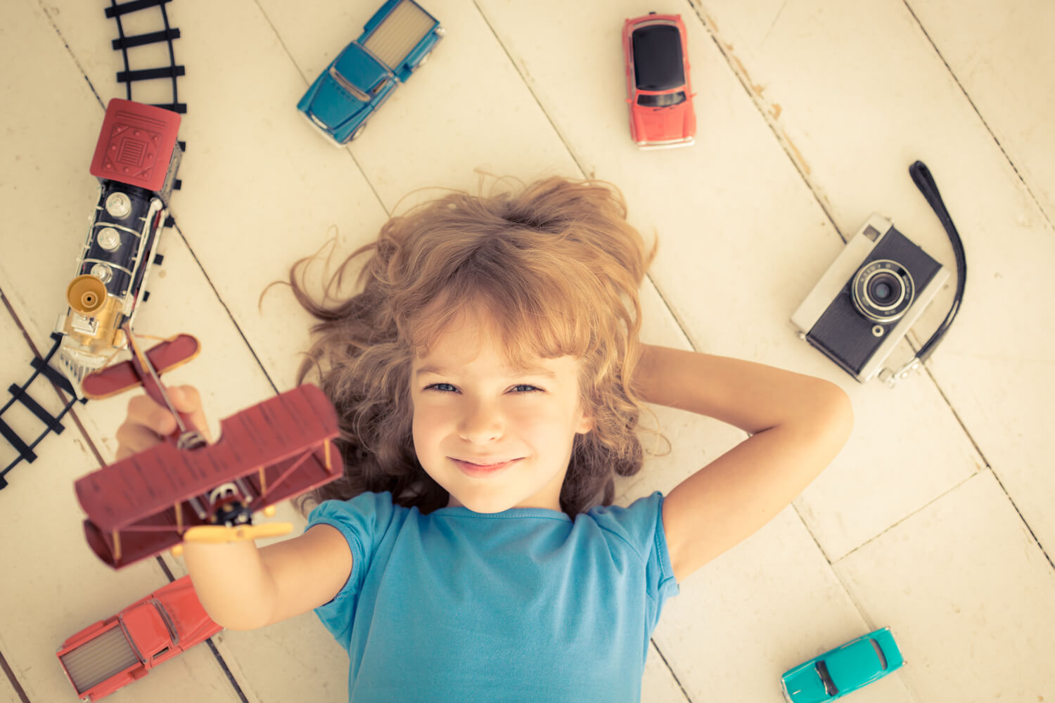 girl playing with vintage car , trains , plane