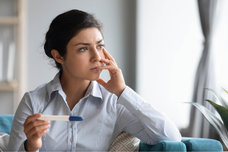 women sad after checking her pregnancy test