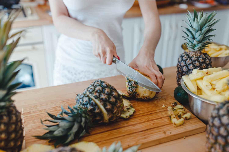 women cutting pineapple