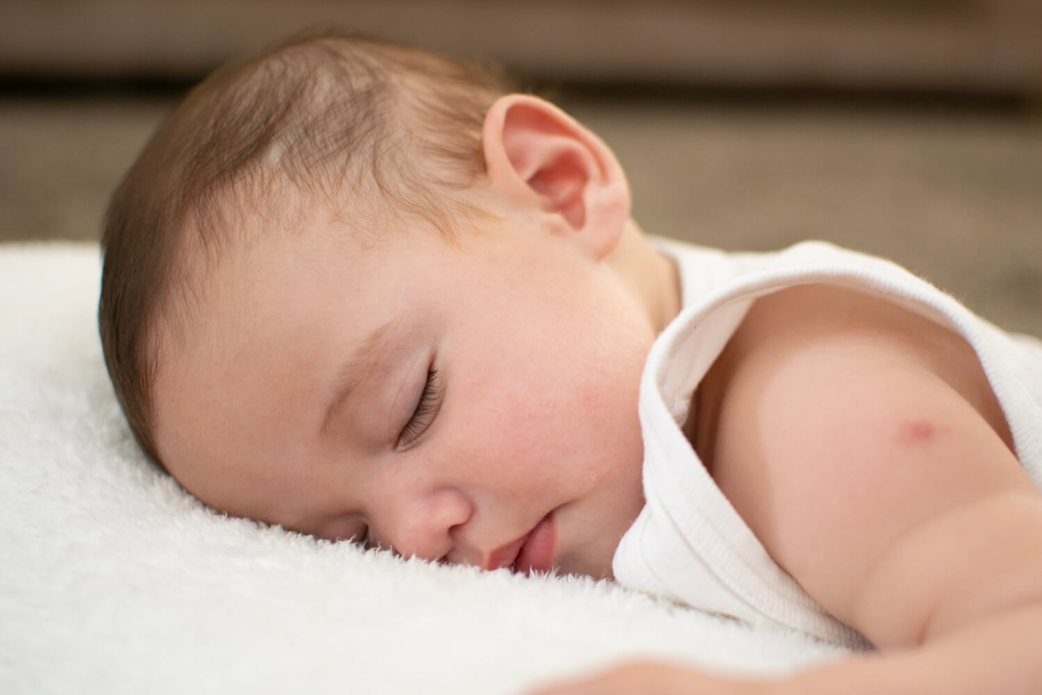 Tired baby sleeping after MMR vaccine