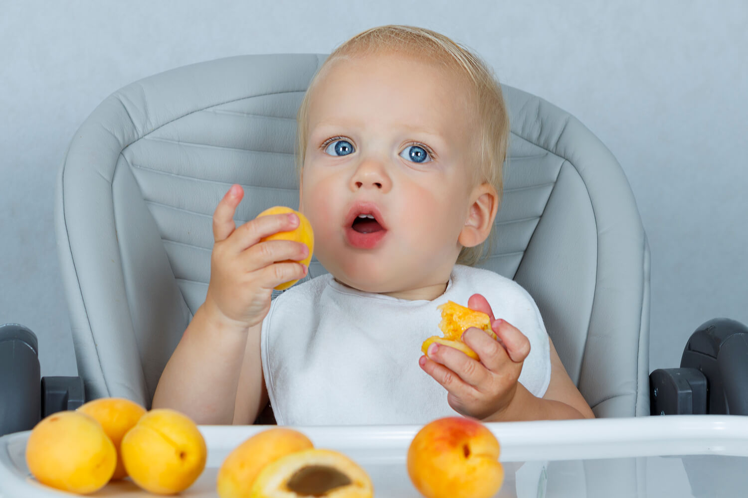 baby eating apricot