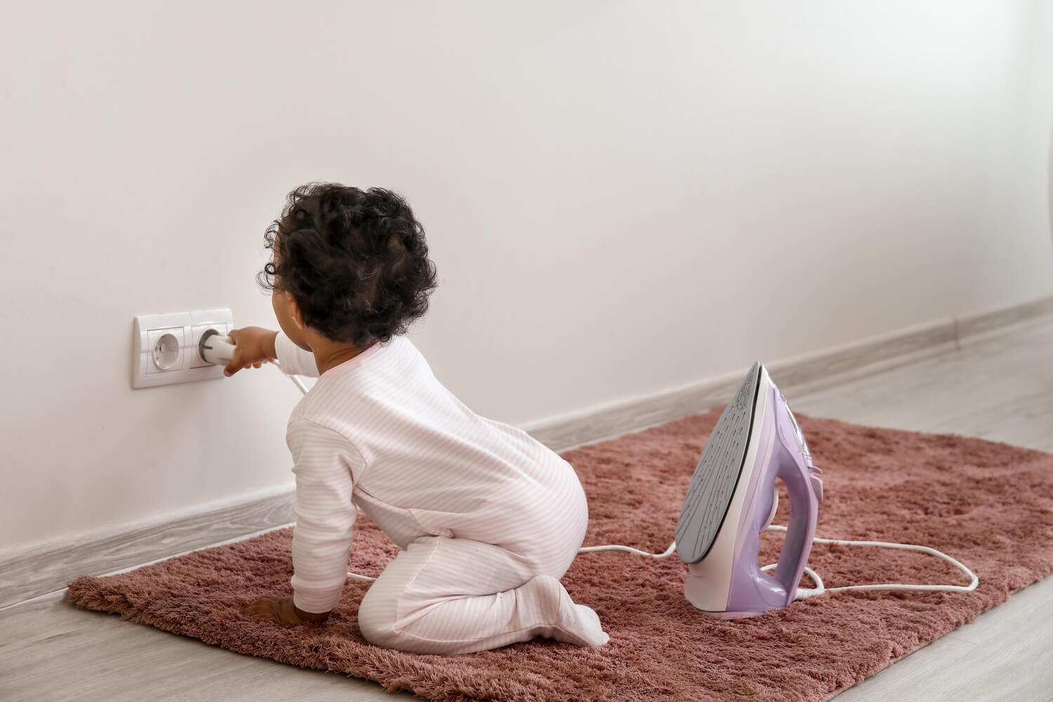 baby playing with socket and iron box