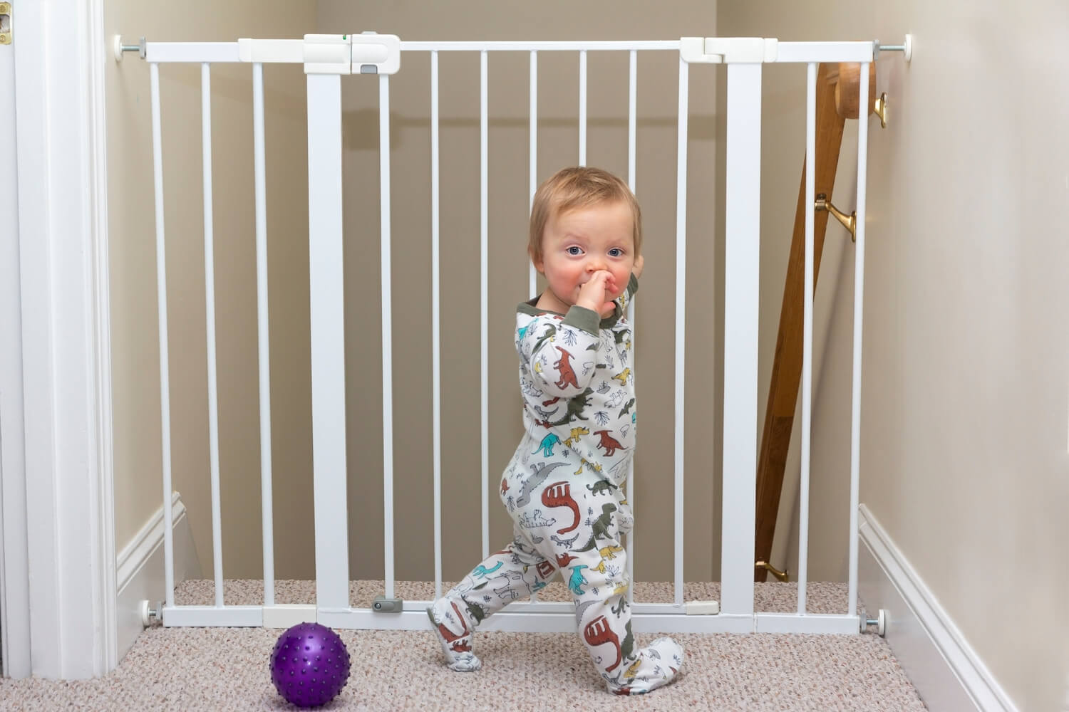 baby standing near baby gate for stairs