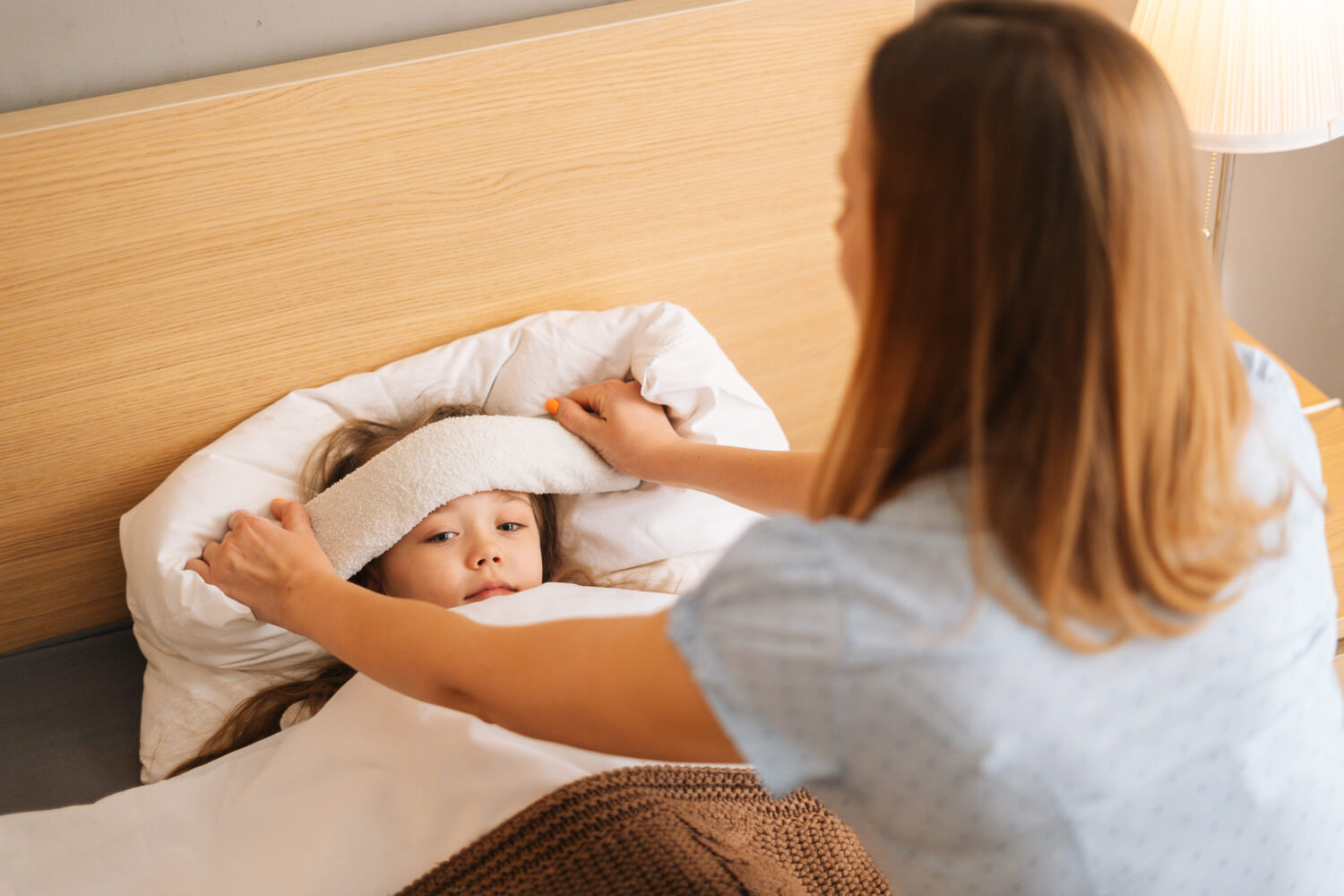 mom putting compress on forehead of sick baby