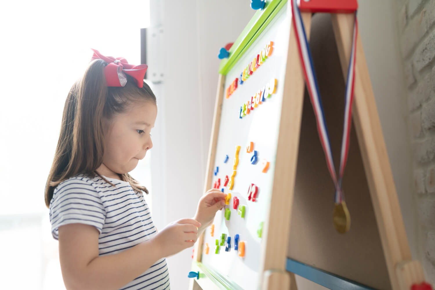 girl playing with magnetic numbers