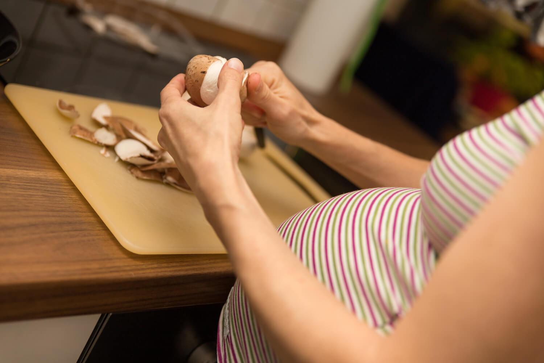 pregnant woman cutting mushroom