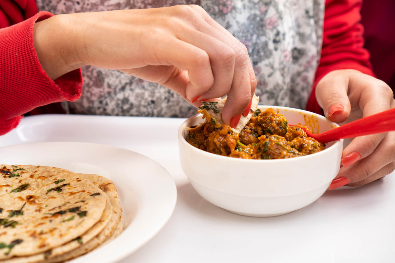 woman eating potato curry