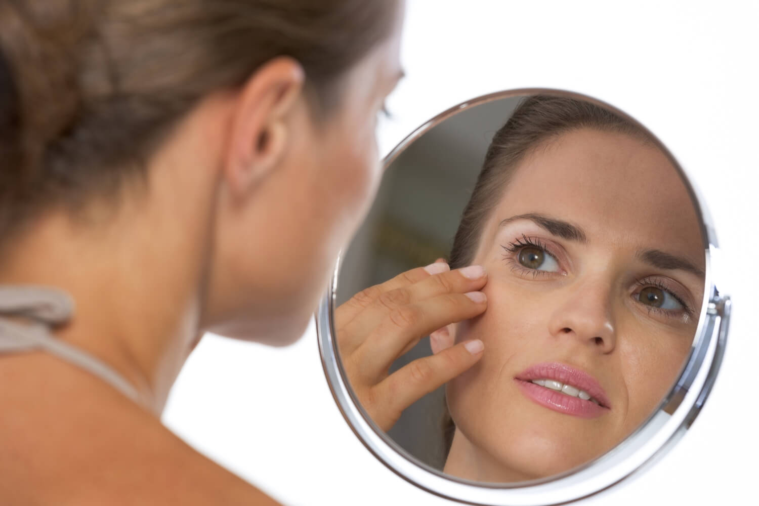 woman looking into face mirror