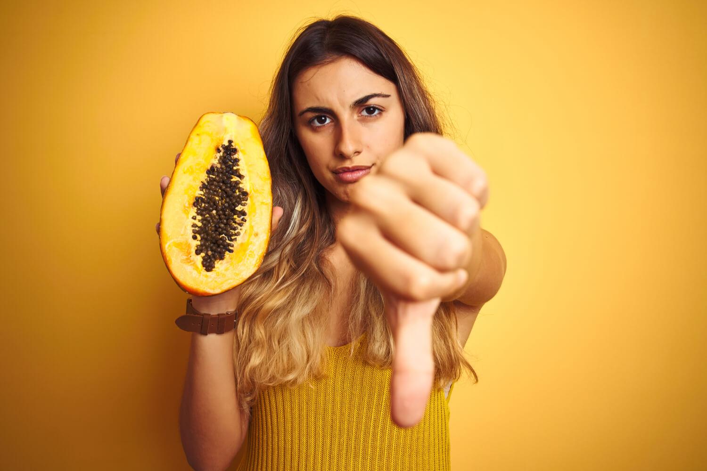 woman thumps down with papaya